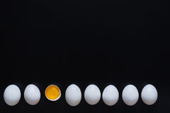 White eggs isolated on black background. White home eggs arranged in a row with one cracked, showing yolk on black background Stock Photography