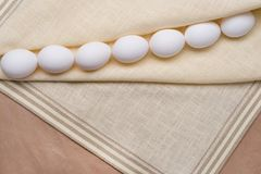 White eggs on a linen tablecloth and old kraft paper. Royalty Free Stock Photography