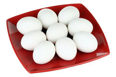 White eggs and red plate Royalty Free Stock Photos