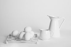 White eggs and white cups on a white background. White eggs in a white metal holder with a small white porcelain cup and a big white metal cup on a white Royalty Free Stock Image