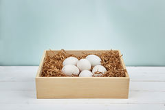 White eggs on a wooden background. White eggs with a wooden box on a wooden background Royalty Free Stock Image