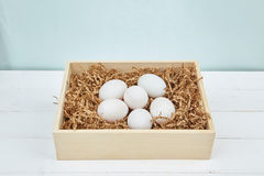White eggs on a wooden background. White eggs with a wooden box on a wooden background Royalty Free Stock Images