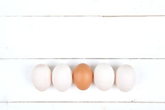 White eggs on a wooden background. White eggs with brown egg in center a wooden background Stock Photo