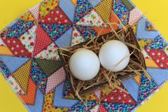 White eggs in a wooden crate, on a patchwork rug, with yellow background stock photography