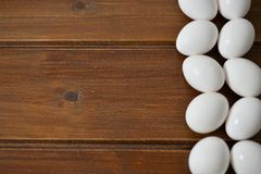 White eggs on wooden plate stock photography