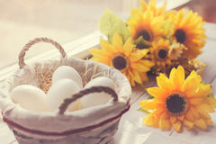 White eggs and yellow flowers stock photos
