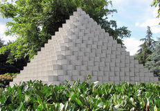 White Egyptian pyramid in the green summer park Royalty Free Stock Photography