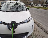 White Electric car charging on the street stock photography