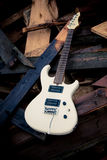 White electric guitar on a woodpile. Old white electric guitar on a woodpile Stock Photography