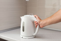 White electric Kettle in hand on the background of the kitchen.  Stock Image