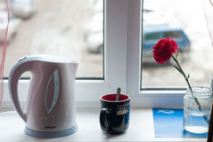 White electric kettle on the windowsill,. A red carnation, ceramic Cup with hot coffee, still life Royalty Free Stock Photos