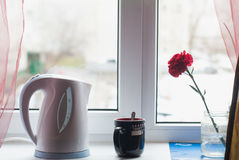 White electric kettle on the windowsill,. A red carnation, ceramic Cup with hot coffee, still life Stock Photos