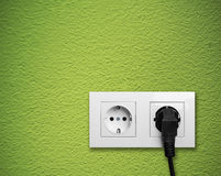White electric outlet mounted on green wall Stock Photo
