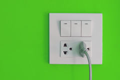 White electric outlet and switch mounted on blue wall Royalty Free Stock Images