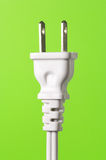 White electric plug on green background (vertical) Royalty Free Stock Photos