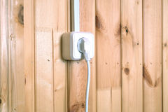 White electric plug in socket on wooden wall with vertical planks Stock Images
