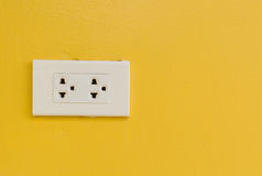 White electric plug on yellow wall. Royalty Free Stock Images