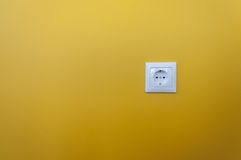White electric plug on yellow wall Royalty Free Stock Images