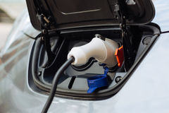 White electrical nozzle charging an electric car Royalty Free Stock Photography