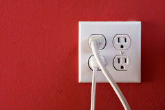 White Electrical Outlets. Electrical outlets with four spaces and two of them have chords plugged in Royalty Free Stock Images