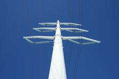 White electricity pylon and the blue sky. White high voltage electricity pylon against the deep blue sky, from below royalty free stock photos
