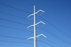 White electricity pylon and power lines. White high voltage electricity pylon and power lines against the deep blue sky stock photography