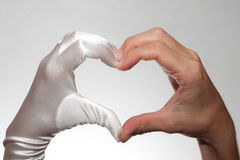 White elegant heart shaped woman's glove and  man's hand isolated on white background. White elegant heart shaped female glove and  man's hand isolated on white Stock Photo