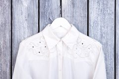 White elegant shirt on hanger. Women fashion apparel on wooden background. Collection of feminine brand outfit Royalty Free Stock Photography