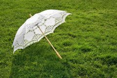 White elegant umbrella on fresh grass Stock Image