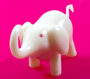 White elephant. A closeup of a white plastic elephant, pink background Stock Image