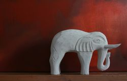 White Elephant. A hand carved white wooden elephant set atop a mantle piec, against a red grunge styled background Royalty Free Stock Photography