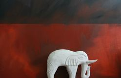 White Elephant. A hand carved white wooden elephant against a red and dark blue grunge styled background Royalty Free Stock Photos