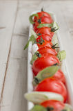 White elongated dish filled with cherry tomatoes and spring onio Royalty Free Stock Photos