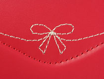 White embroidery in the shape of a bow on pink leather Stock Photo