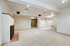 White empty basement room with fireplace. And wall to wall carpet floor. Northwest, USA Royalty Free Stock Photos