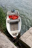 White empty boat with oars on the water near concrete beach. A fishing boat with oars on the water of a lake near the shore with a concrete slab Stock Image