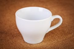 White empty Cup on sacking closeup Royalty Free Stock Images