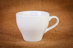 White empty Cup on sacking closeup Stock Images