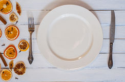 White empty dining plate with cutlery on a white wooden surface Stock Image