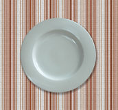 White empty dinner plate. Top view of a white dish on a textured background Stock Photos