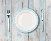 White empty dinner plate with blue border on wooden table stock photos