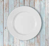 White empty dinner plate on blue wooden table stock image