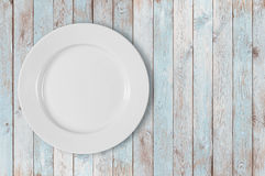 White empty dinner plate on left side of blue wooden table royalty free stock images