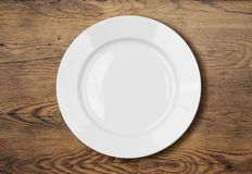 White empty dinner plate on wooden table surface Stock Photos