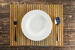 White empty dish on bamboo weave and wooden table background Stock Photos