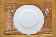 White Empty Dish With Spoon and Fork Set. On Thai Mat Wooden Desk Royalty Free Stock Images
