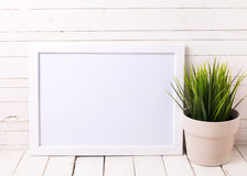 White empty frame and grass in pot on white wooden background. Stock Images