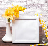 White empty frame with place for text or picture on the table wi. Th yellow flowers in a vase and striped paper straws in a glass. Mock up Stock Photography