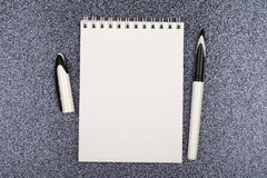 White empty notebook with pen on black. royalty free stock photography