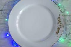 White empty plate with christmas illumination around. White empty plate with christmas illumintation around on white rustic background Stock Photos